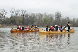 two groups of students in canoes on a river