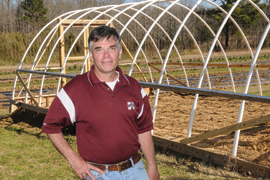 scientist standing in front of high hoop house